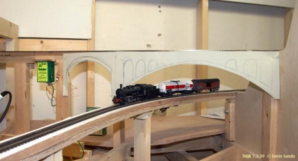 """Prøvetoget smyger seg fint under Olmli-viadukten med """"skisse"""" for hvordan broa skal bli."""