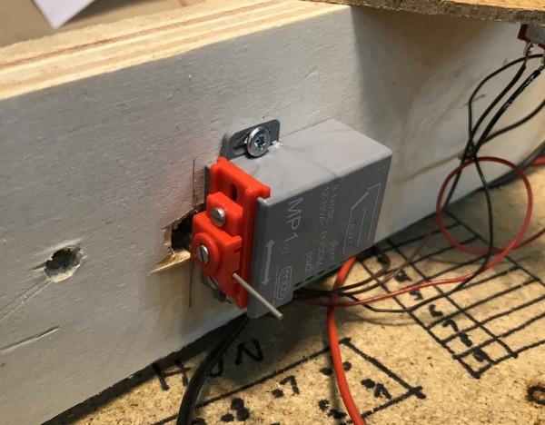 Det er bare 3 cm klaring under, så det var en lang diskusjon om hva slags sporveksler / sporvekselmotorer vi måtte bruke. Det ble foreslått oppåliggende motorer med dobbeltspole av den tradisjonelle typen fra mange tiår tilbake. Da vi imidlertid hadde mer enn nok med Pecos lange veksler liggende, så vi oss om etter underliggende motorer som ikke bygger mer enn 3 cm, helst mindre. Det tsjekkiske firmaet MTB leverer to nette slike, MP1 (1 kontaktsett) og MP5 (2 kontaktsett) som ble kjøpt inn på prøve, og også tilsvarende lavbyggende fra Tillig. Den fra TIllig ble forkastet fort fordi alt av mekanikk og kontakter ligger helt åpent. Det er ikke særlig egnet i et roma der det tidvis vil støves til med trearbeider. Valget falt på den billigste og minste utgaven til MTB, nemlig MP1 med ett kontaktsett som vi bruker til å mate skinnekrysset. HVis vi skulle trenge tilbakemelding av posisjonen, kan vi bruke et hjelperelé i tillegg, og det kommer til sammen billigere ut enn å gå for den 60,- dyrere MP5. Bildet viser en prøvemontering av en MP1. Den virker å være veldig lett å justere siden den etter at festeskruene er montert, kan forskyves i begge planene. Utslaget kan endres mekanisk inne i motoren. Vi valgte 3 mm utslag.